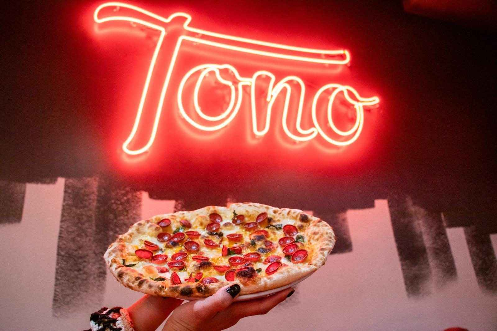 A person holding up a pizza in front of a neon sign that says
