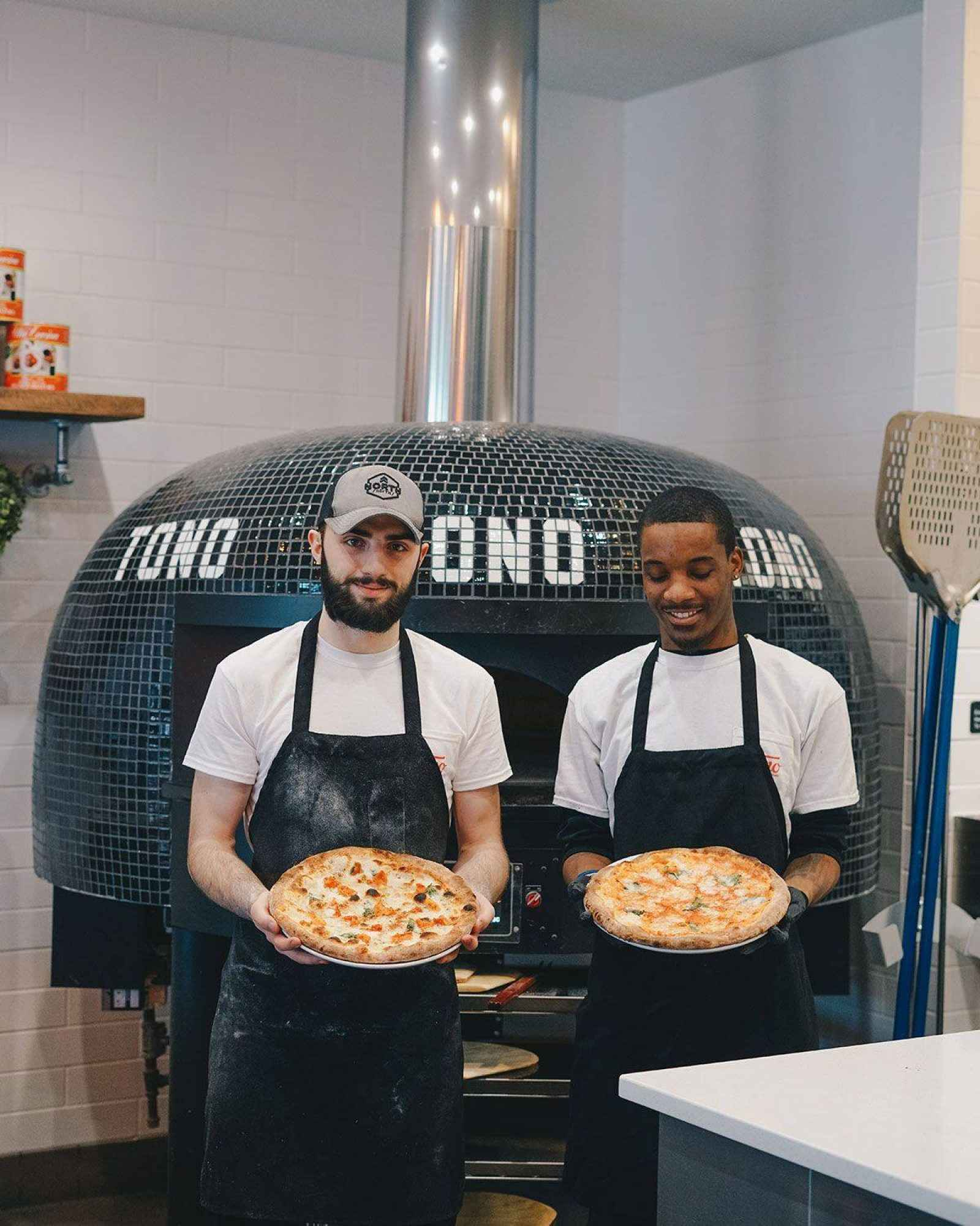 Two Tono employees standing in front of the Tono pizza oven holding pizzas
